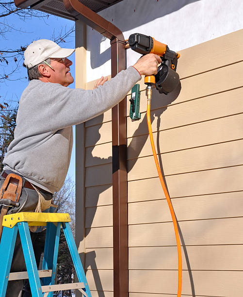 Man installing siding with nail gun stock photo