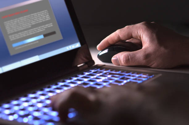 Man installing software in laptop in dark at night. Hacker loading illegal program or guy downloading files. Man installing software in laptop in dark at night. Hacker loading illegal program or guy downloading files. Cyber security, piracy or virus concept. pirate criminal stock pictures, royalty-free photos & images