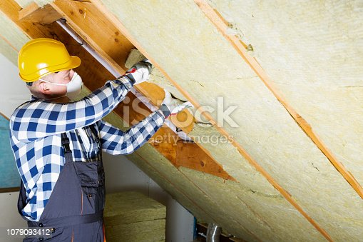 istock Man installing thermal roof insulation layer - using mineral wool panels. Attic renovation and insulation concept 1079093412