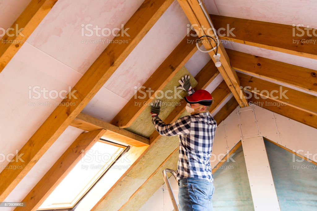 Man Installing Thermal Roof Insulation Layer Using Mineral Wool
