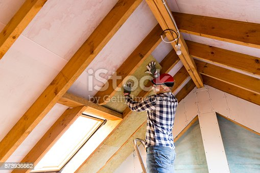 istock Man installing thermal roof insulation layer - using mineral wool panels. Attic renovation and insulation concept 873936662