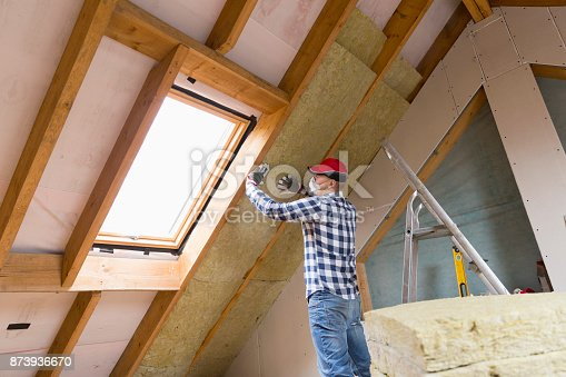 istock Man installing thermal roof insulation layer - using mineral wool panels. Attic renovation and insulation concept 873936670