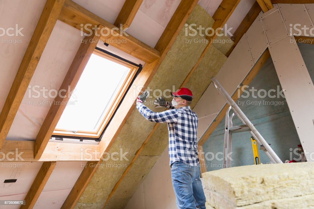 Man installing thermal roof insulation layer - using mineral wool panels. Attic renovation and insulation concept stock photo