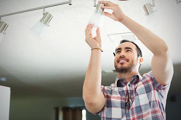 mann installiert beleuchtungskörper in neues zuhause - glühbirne auswechseln stock-fotos und bilder