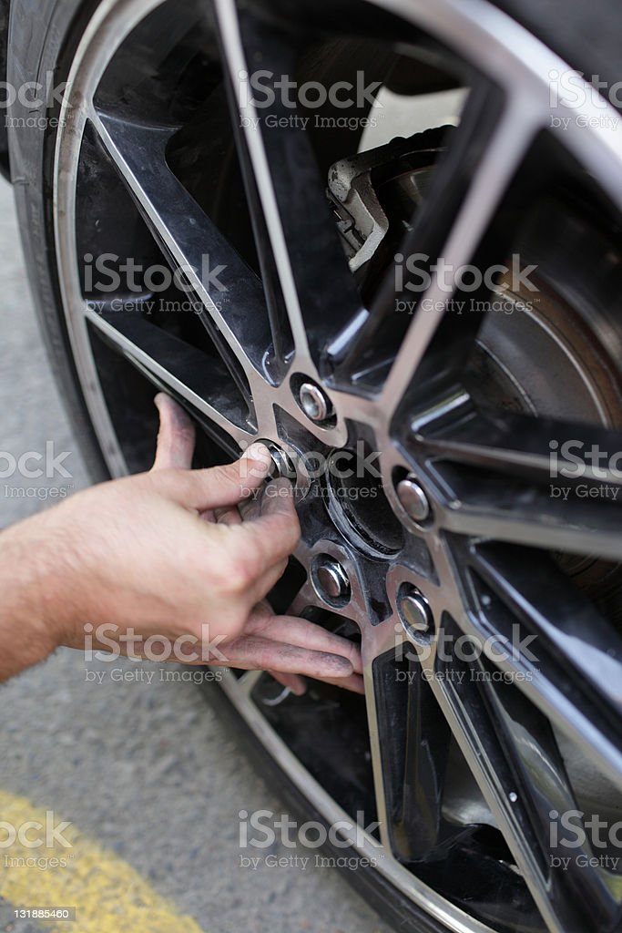Man installs spare wheel royalty-free stock photo