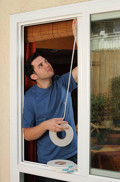 man installs weather stripping in window - weather stock photos and pictures