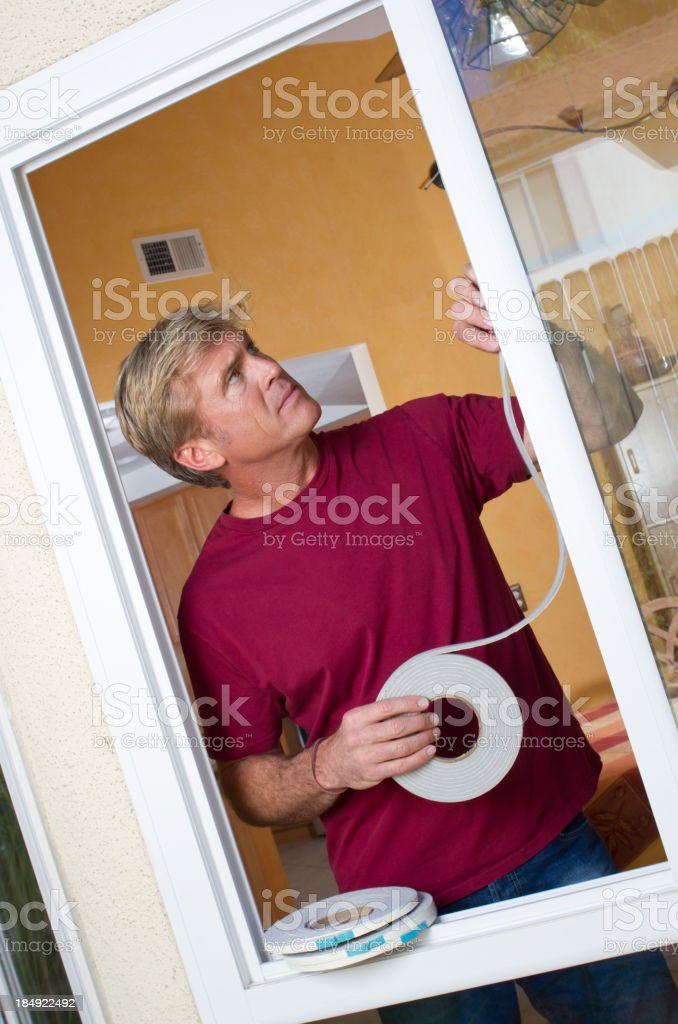 Man Installs Weather Stripping Tilt Left stock photo