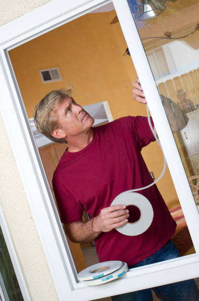 """Man Installs Weather Stripping Tilt Left """"Homeowner lowers his energy bills by applying weather stripping to his kitchen window.Professional model shot in 2011 in Moreno Valley, California."""" undressing stock pictures, royalty-free photos & images"""