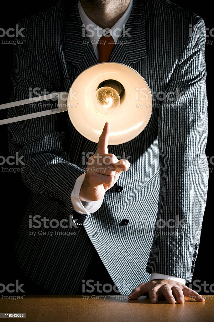 Man interrogating someone and shining a light on them stock photo