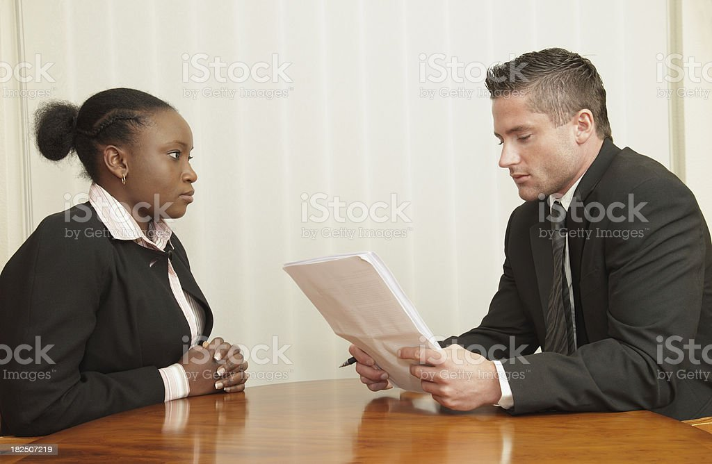 Man Interviewing Woman A man looks over a woman's CV in a job interview.Similar images in my portfolio: Adult Stock Photo