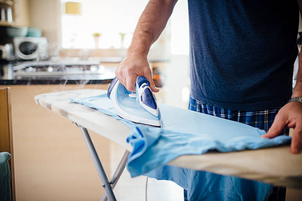 man ironing laundry - ironing stock photos and pictures