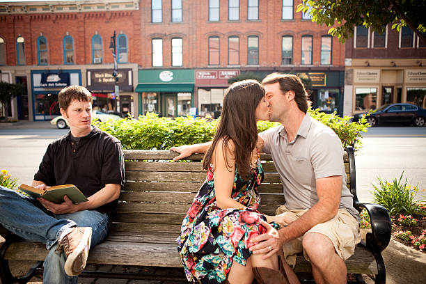 Man Irritated with Couple Kissing on Bench Downtown stock photo