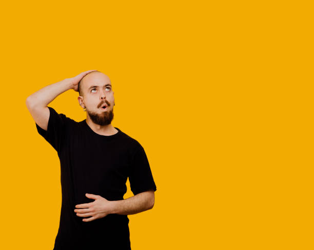 man is amazed, with opened mouth and hands on head and belly in black t-shirt looking upstairs, positive human emotion facial expression, isolated on yellow background - omg stock photos and pictures