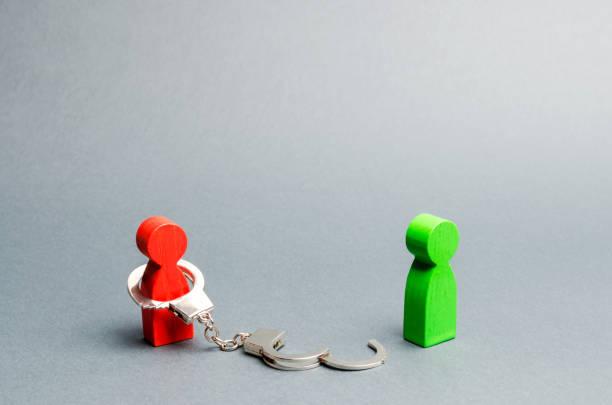 Un homme est lié par des menottes debout près d'une personne libre. Exonération de la dette ou de l'esclavage physique. Séparation ou divorce de deux personnes. La fin de la relation. Exonération des obligations. - Photo