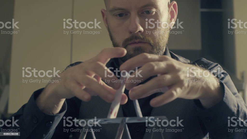 A man is building a house of a playing cards. stock photo