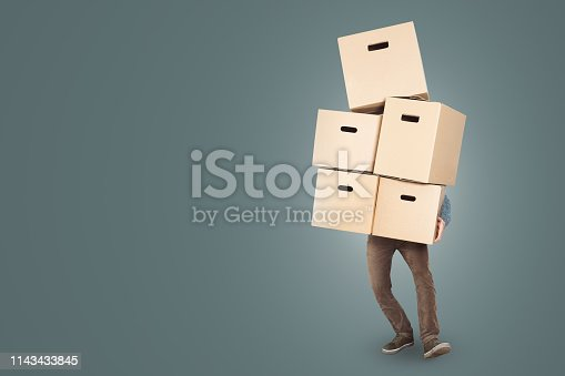 A man is carrying five cardboard moving boxes at once. The upper body is hidden behind the boxes with only the legs and one arm visible. Copy space included. Isolated on a neutral color.