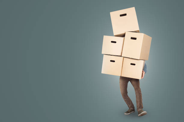 A man is carrying a big stack of cardboard boxes in his arms A man is carrying five cardboard moving boxes at once. The upper body is hidden behind the boxes with only the legs and one arm visible. Copy space included. Isolated on a neutral color. carrying stock pictures, royalty-free photos & images