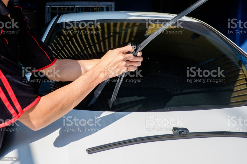 Man is changing windscreen wipers on a car – zdjęcie
