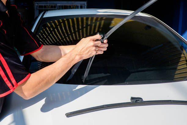 Man is changing windscreen wipers on a car Man is changing windscreen wipers on a car, Asian man installing new windshield wipers by himself at home windshield wiper stock pictures, royalty-free photos & images