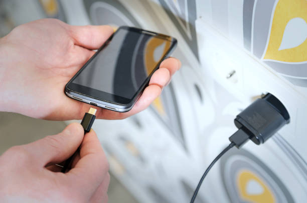 A man is charging the smartphon. A man is inserting a power cord into the mini USB for charging the smartphone. phone charging stock pictures, royalty-free photos & images