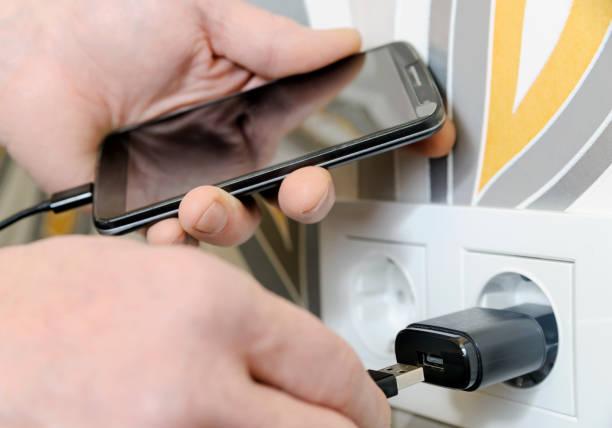 ein mann wird das smartphon geladen. - usb kabel stock-fotos und bilder
