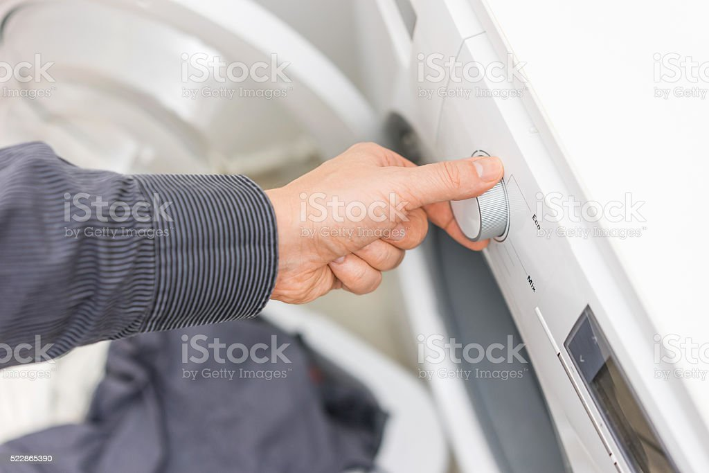 Man is choosing Eco Program on the Washing Machine, stock photo