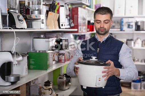 Man is choosing multivariate for his kitchen in store.