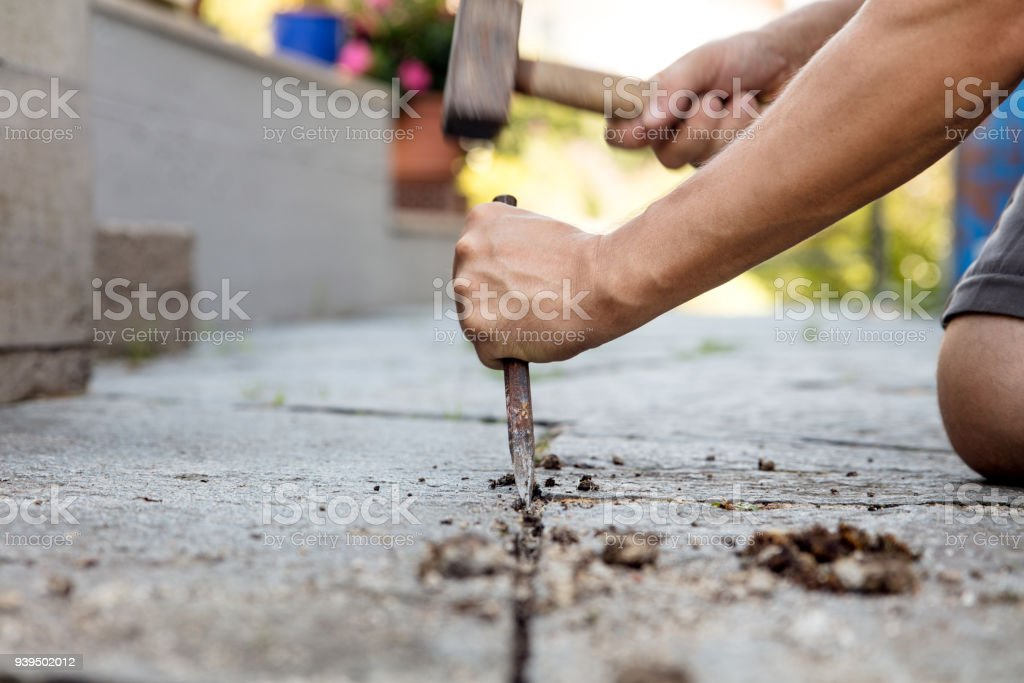 man is cleaning the mortar joints of a flagstone floor with stone mason tools, like hammer and chisel, preparing for fresh grouting stock photo