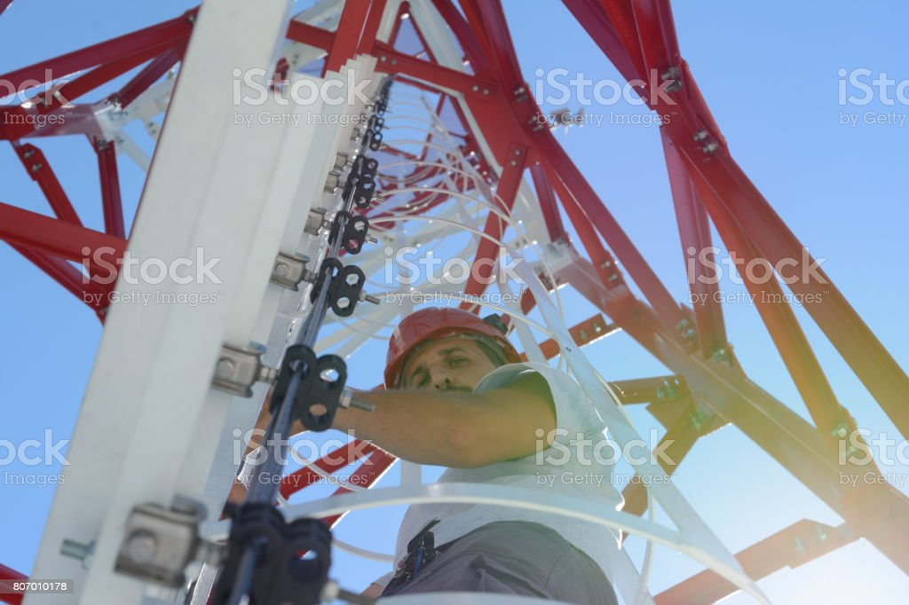 Man is climbing a high power electric line tower stock photo