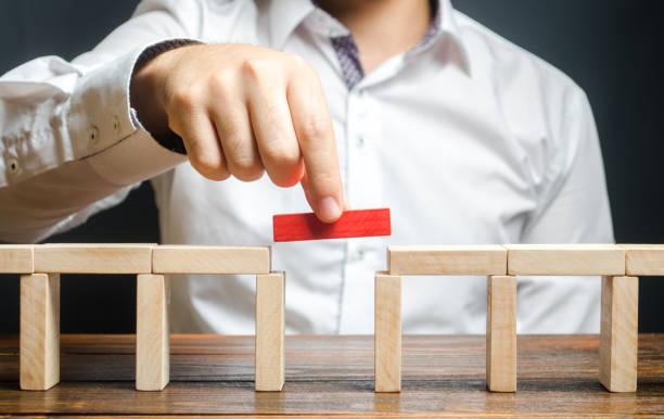 een man is het voltooien van de bouw van een brug. bouw bruggen, maak connecties en nuttige contacten. het verbeteren en ontwikkelen van een bedrijf. nieuwe innovatieve oplossingen, groei en welvaart - brug mens gemaakte bouwwerken stockfoto's en -beelden
