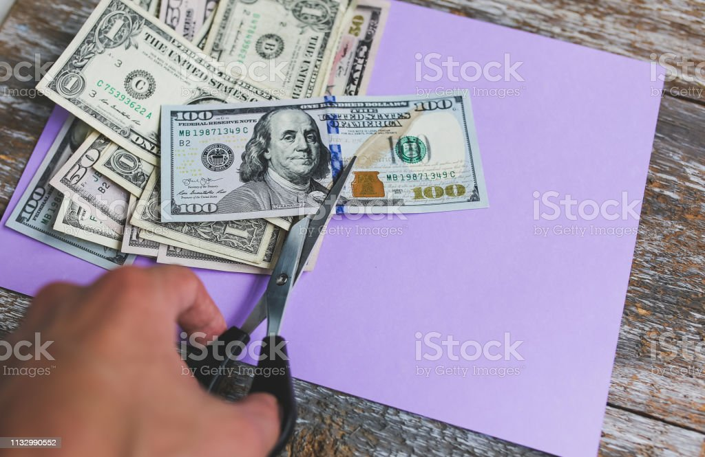 Man is cutting dollar banknotes with scissors on the purple pastel...