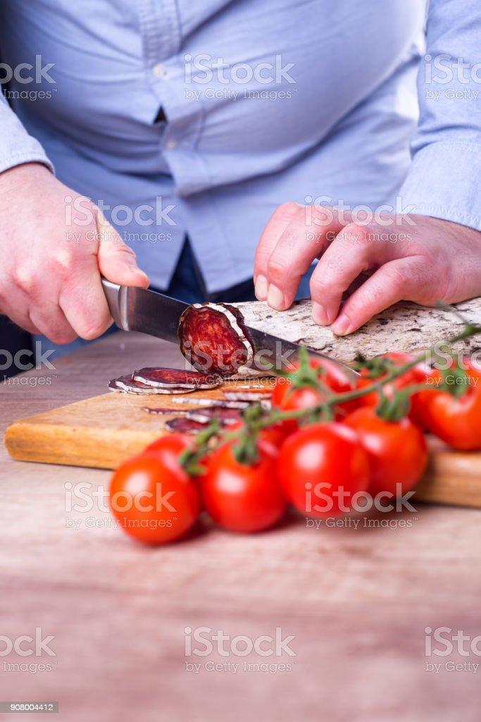 Man is cutting sausage stock photo