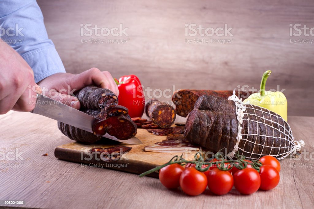 Man is cutting smoked meat stock photo
