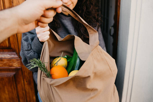 a man is delivering a bag of vegetables and fruit - grocery home foto e immagini stock