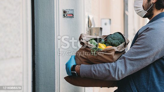A man is delivering a bag of vegetables and fruit.  He's waiting for the customer to open the door.