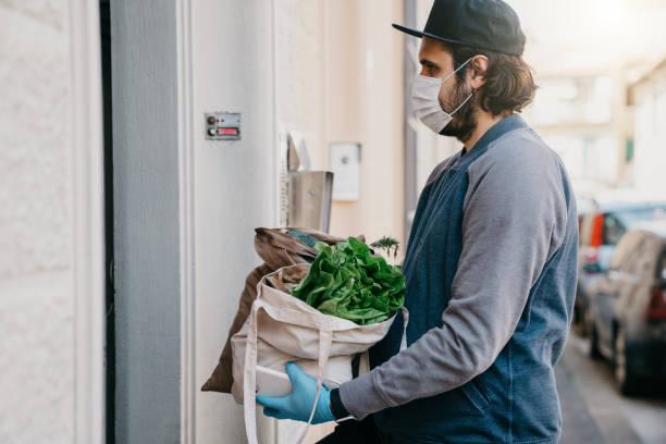 a man is delivering a bag of vegetables and fruit - supermarket worker imagens e fotografias de stock