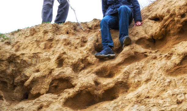 Man is descending from a sandy slope Man is preparing to descend from a sandy slope deathly stock pictures, royalty-free photos & images
