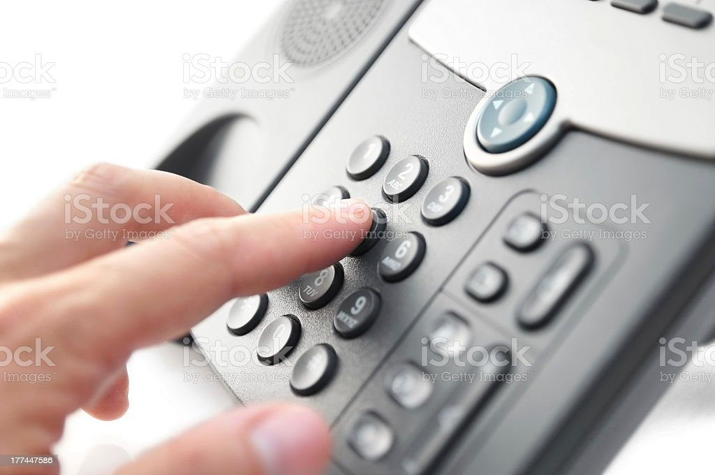 A man is dialling on a landline phone stock photo