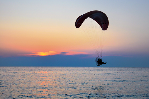 A man is doing paragliding on the mediterranean sea at sunset
