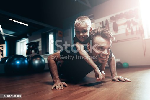 997711042istockphoto Man Is Doing Push Ups In Gym With Son On A Back. 1049284288