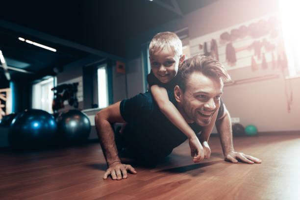 Mann tut Push Ups In Turnhalle mit Sohn auf dem Rücken. – Foto
