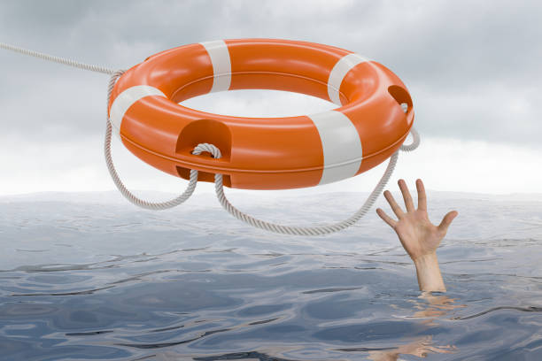Man is drowning in ocean and is catching life buoy. stock photo