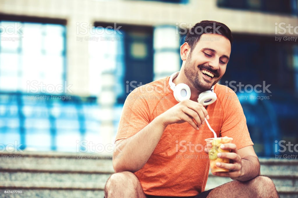 Man is eating after jogging stock photo