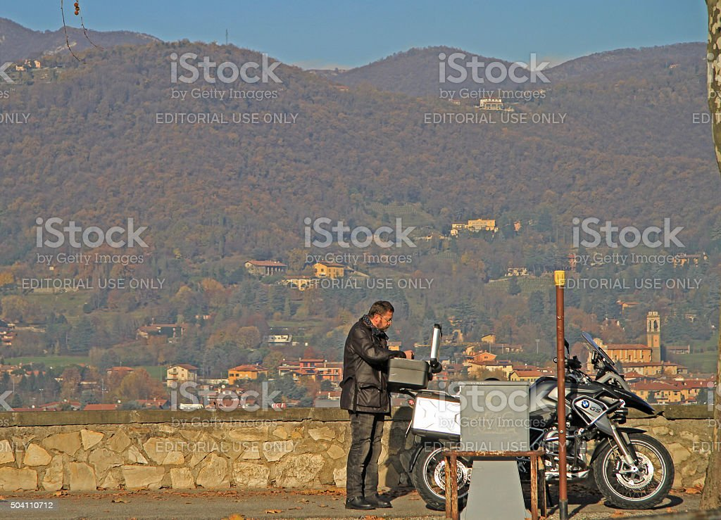 man is eating against the background of hills in Bergamo stock photo