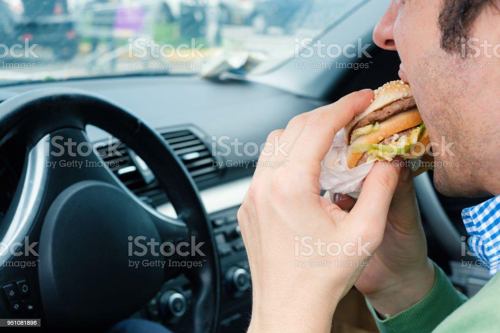 Man is eating hamburger while driving his car stock photo