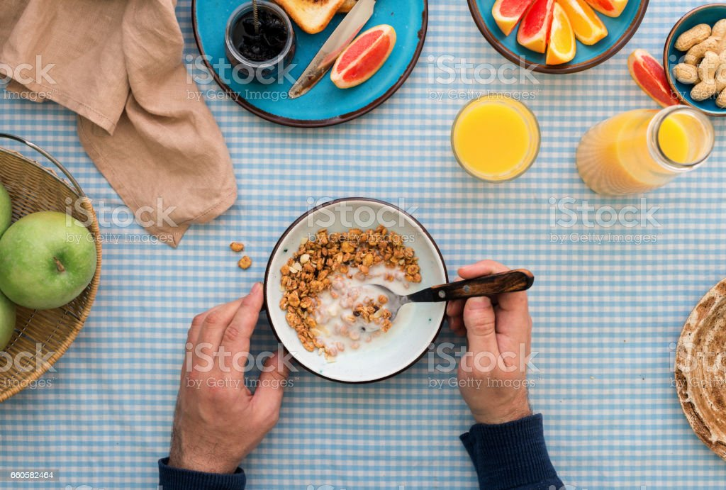 Man is eating muesli with yogurt, top view stock photo