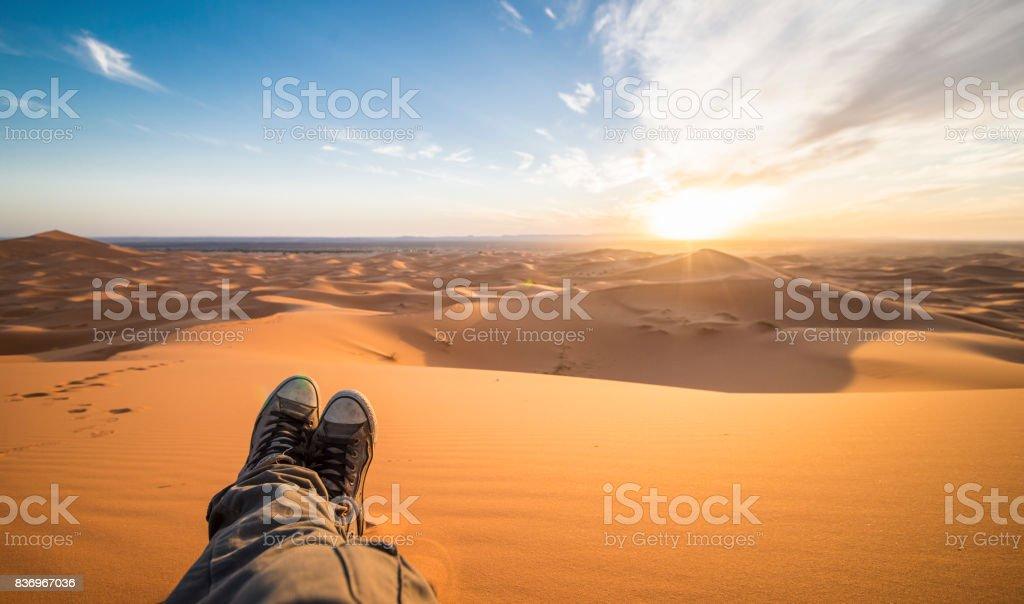 Ein Mann genießt den Sonnenuntergang in den Dünen in der Wüste Sahara - Merzouga - Marokko – Foto
