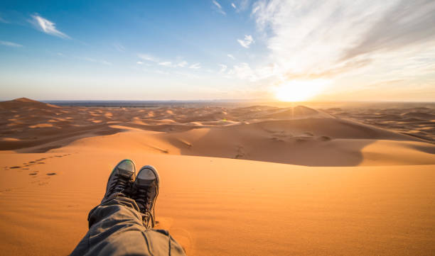 A man is enjoying the sunset on the dunes in the Sahara Desert - Merzouga - Morocco stock photo
