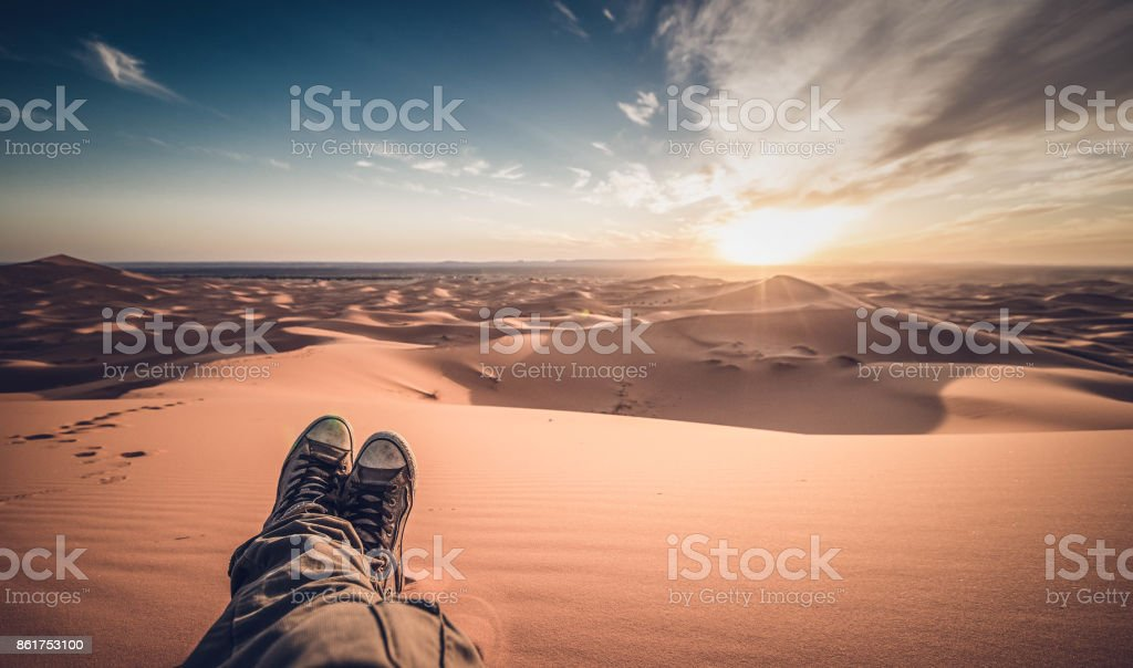 A man is enjoying the sunset on the dunes in the Sahara Desert - Merzouga - Morocco stock photo