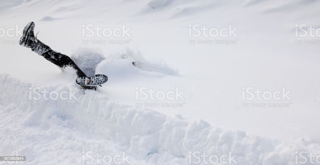 Man is falling headfirst into deep snow. Concept of winterly slippery conditions. stock photo